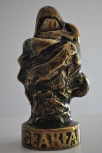 Statuetka z brązu, przypomina wędrowca owiniętego suknem z kapturem na głowie